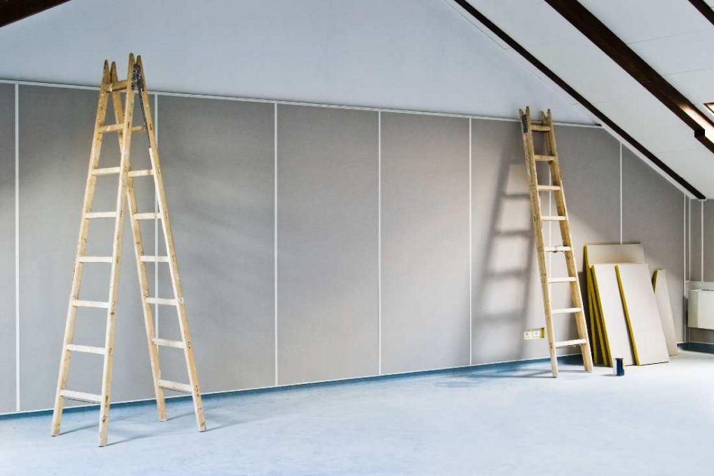 long wooden ladders standing upright in a room