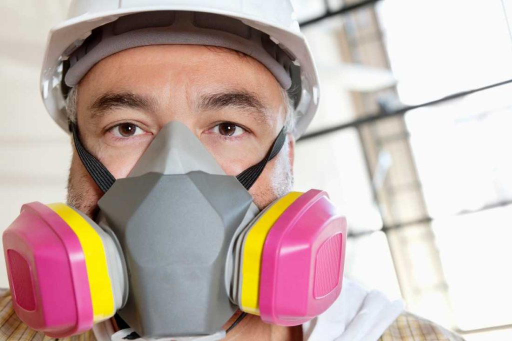 construction worker wearing a pink and yellow dust mask