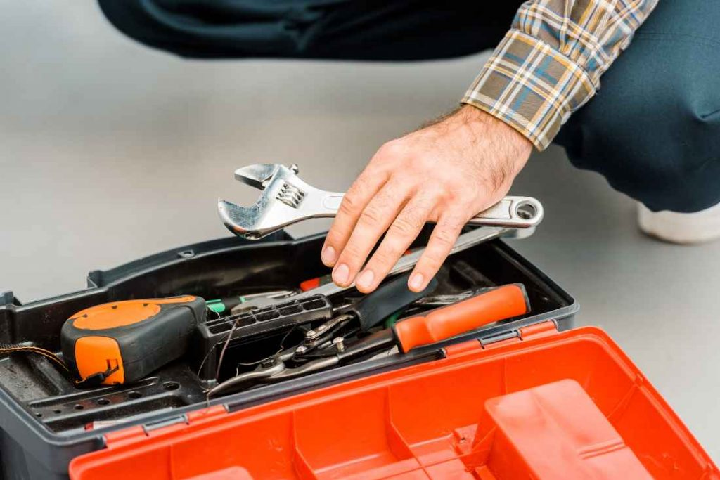toolbox with man holding a spanner in hand
